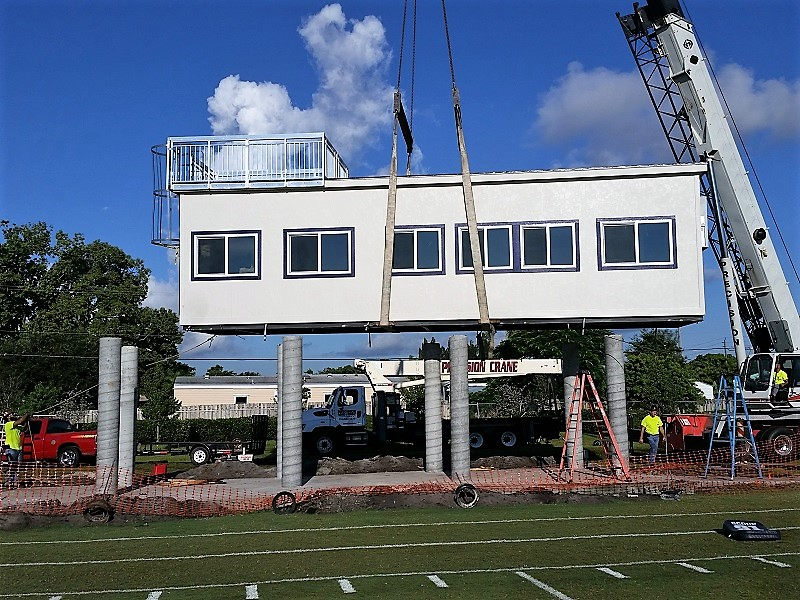 Crane moving modular pressbox into place