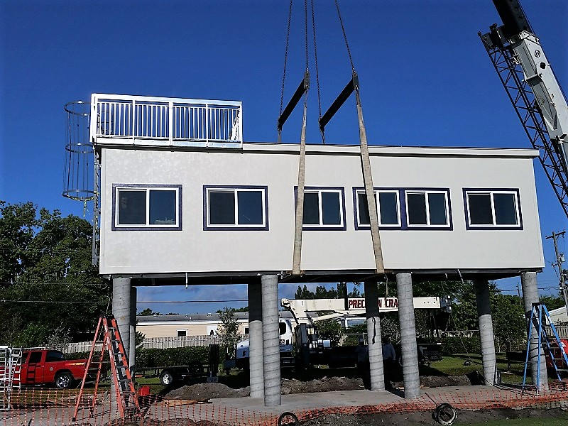 Crane setting modular pressbox onto cement columns