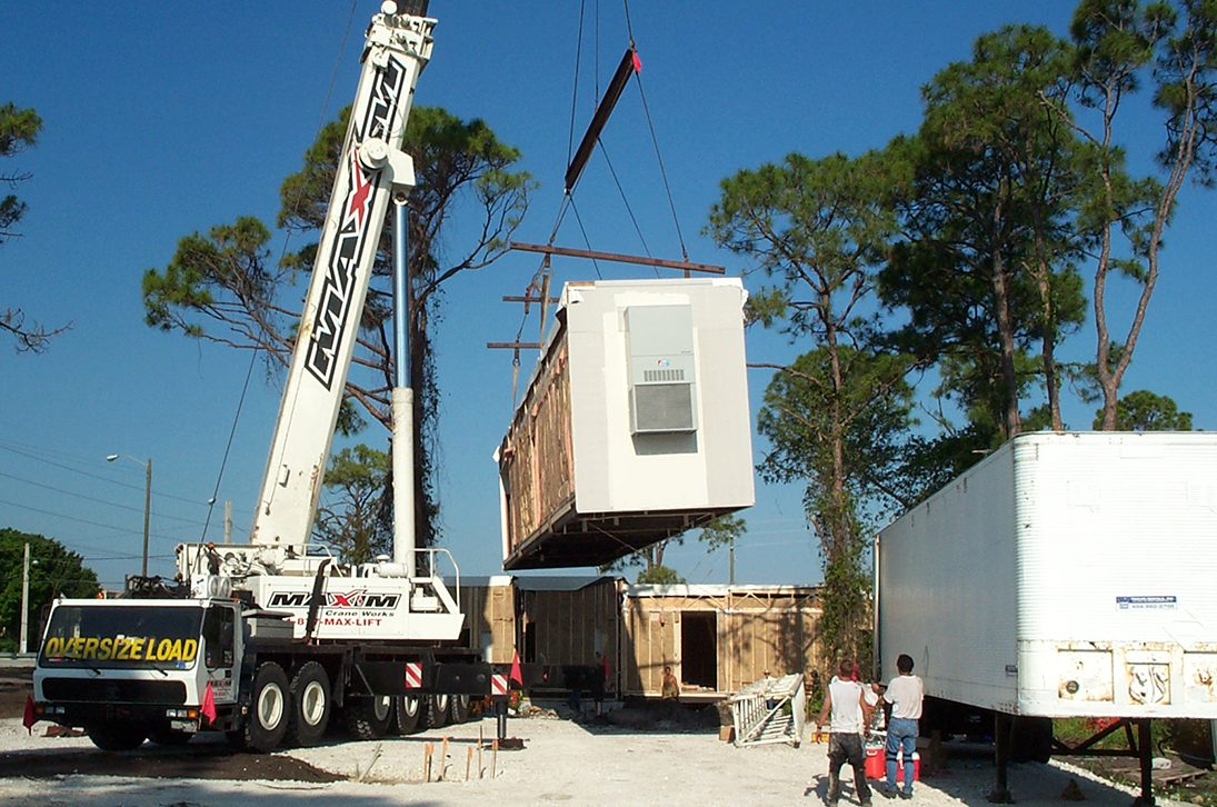 A crane lowering a modular building into place.